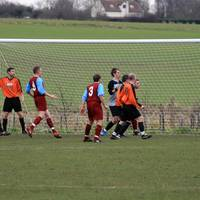 Players watch as the ball eludes the Hempnall forw